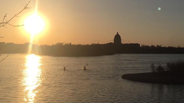 Deux kayakistes devant un coucher de soleil sur le lac Wascana à Regina, en Saskatchewan.