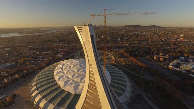 Le stade olympique vu de haut, illuminé par le soleil levant, avec la ville de Montréal en arrière-plan.