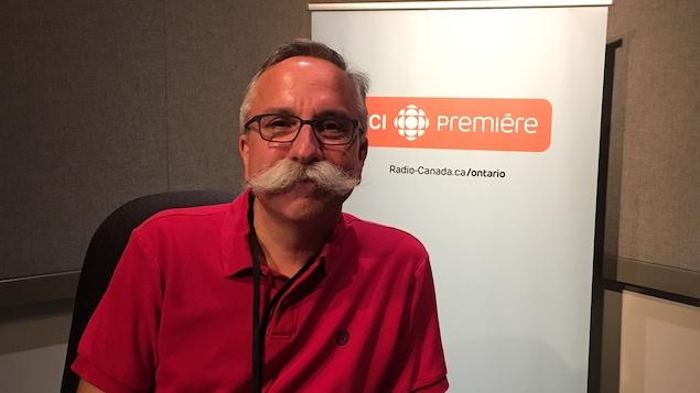 Stéphane Deschênes pose devant une bannière de Radio-Canada