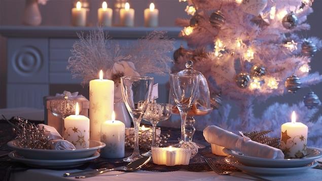Une table dressée pour Noël dans des couleurs blanches et argentées avec des bougies et un sapin qui brille en arrière-plan.