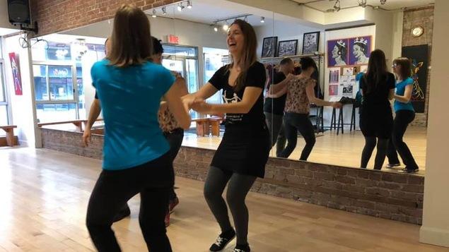 Dans un studio de danse, devant un mur miroir, des danseurs pratiquent le swing