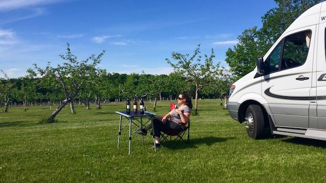 Une touriste pose près d'un verger, en buvant du vin près de son véhicule récréatif