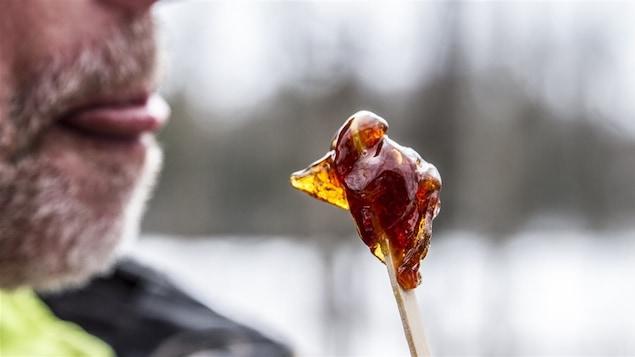 Un bâtonnet de tire d'érable avec une bouche prête à lécher le tout.