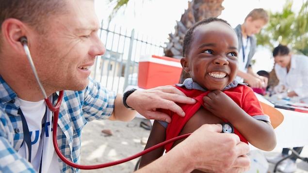 Un médecin soigne un enfant dans un pays du sud.