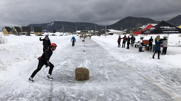 On voit une patinoire longiligne où des patineurs sont en pleine course