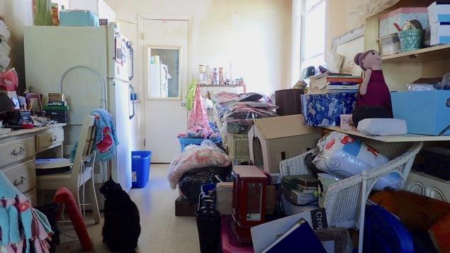 Un petit appartement rempli d'objets divers empilés les uns sur les autres qui couvrent presque tout le plancher.