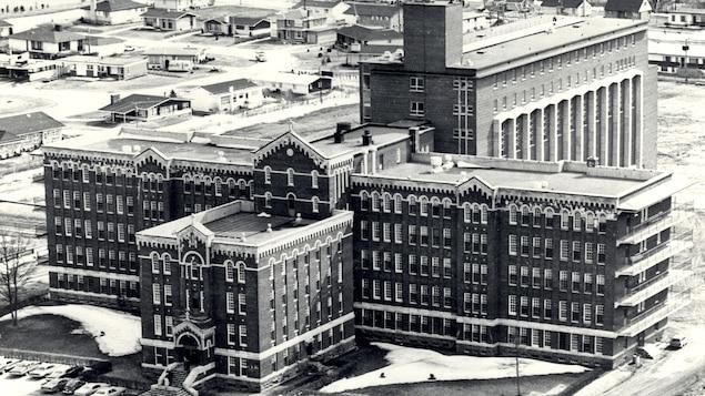 Photo aérienne d'un grand bâtiment de cinq étages en briques qui forme une croix, vu de haut.