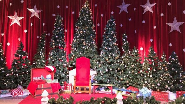 Décor de Noël. Des sapins sont placés derrière le fauteil réservé au père Noël.
