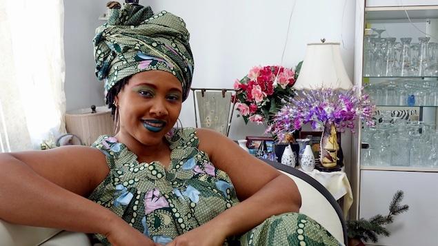Une femme est assise sur un divan dans un salon. Des bouquets de fleurs se trouvent derrière elle. Elle porte un foulard sur sa tête. Elle prend la pause pour le photographe.