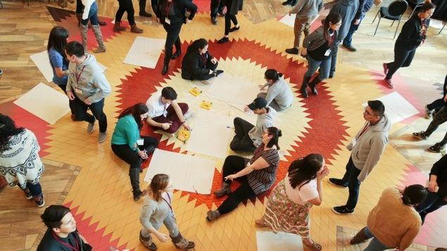 Des dizaines de personnes, vues de haut sur un plancher de mosaïque jaune et rouge
