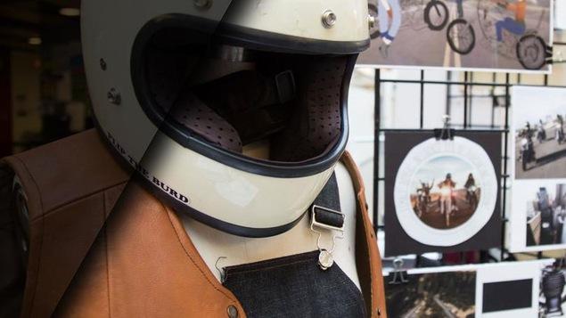 Un mannequin porte un casque de moto, une salopette et une veste sans manche en cuir.