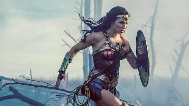 L'actrice Gal Gadot dans le costume de Wonder Woman, court dans une forêt enfumée, bouclier sur la bras gauche.