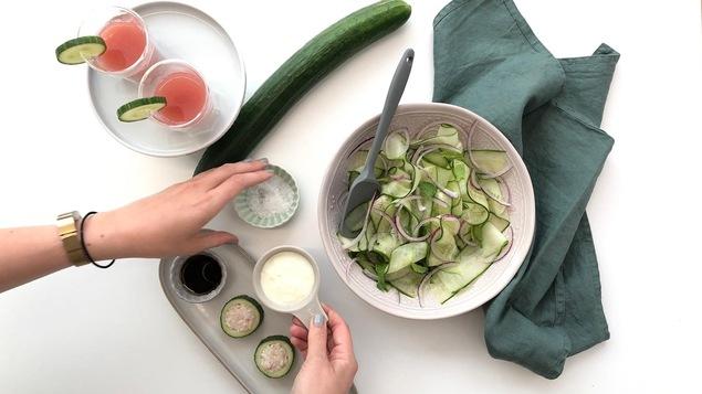 """Vue en plongée de verres de jus de concombre et de pastèque, des """"sushis"""" de concombres et une salade de rubans de concombre avec une main qui tend de la vinaigrette."""
