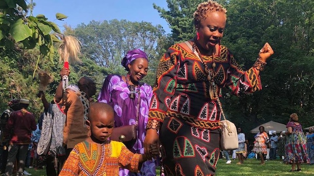 Un enfant et des femmes du peuple Bamiléké dansent.