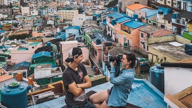 Alex Normand et MJ Lalande, d'Alex & MJ On the Go  posent pour une photo avec les toits de la ville de Busan, en Corée du Sud en arrière-plan.