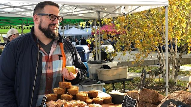 Simon A. Thibault regarde un comptoir de pâtisseries dans un marché extérieur.
