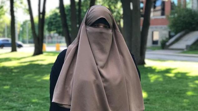Photo de Zineb Benrochd portant un voile qui laisse voir seulement ses yeux.
