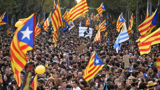 Une foule de manifestants brandissent des drapeaux catalans dans les rues de Barcelone, en Espagne.