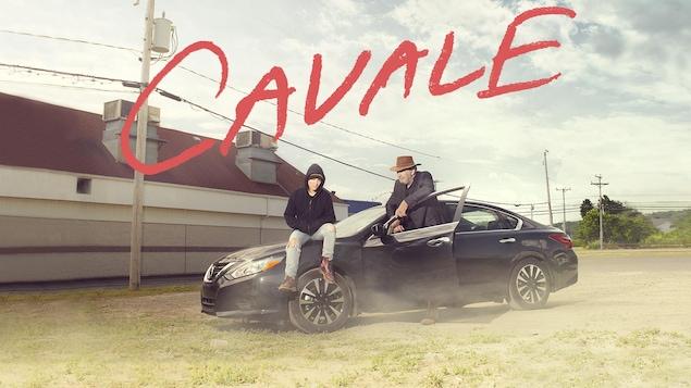 Les comédiens Gildor Roy et Catherine Brunet devant une voiture noire