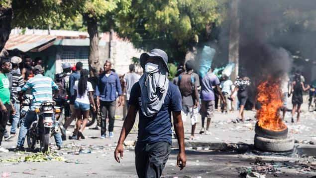 Des pneus en feu dans les rues de Port-au-Prince, à côté de déchets et de gens qui marchent.