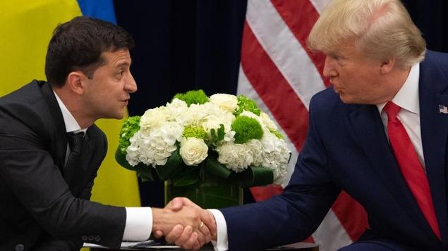Deux hommes en complet se serrent la main devant un pot de fleurs et les drapeaux américains et ukrainiens.