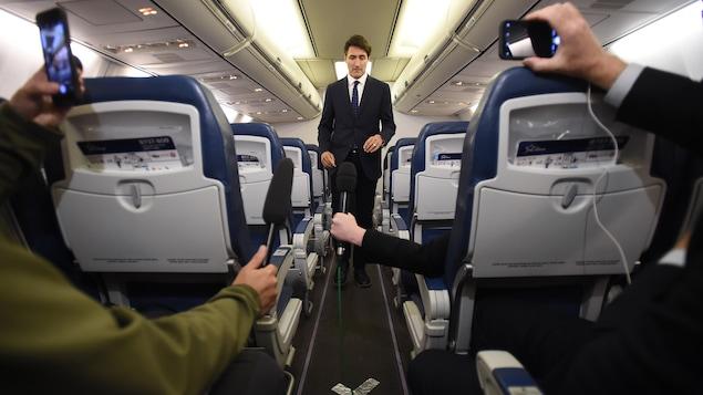 Un homme en complet cravate regarde vers le sol alors qu'il se faufile dans l'allée centrale d'un avion. Au fond de l'avion, des journalistes tendent le micro vers lui.