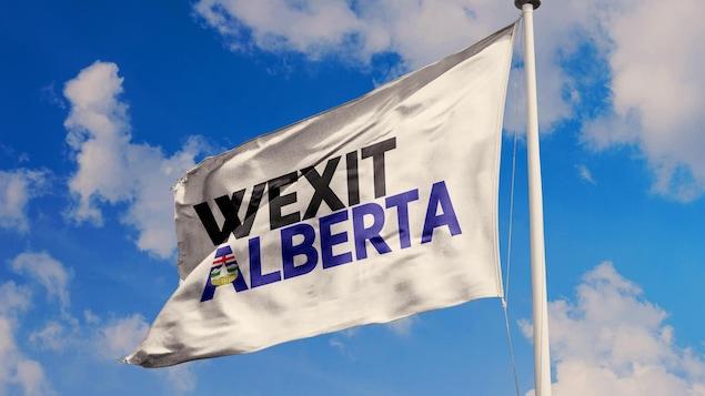 Un drapeau représentant le wexit albertain flotte dans un ciel bleu avec quelques nuages.