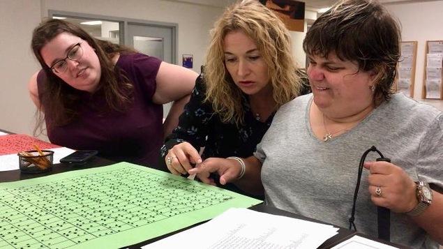 Trois femmes regardent une affiche sur laquelle est imprimé du braille.