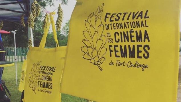 Des sacs avec un logo du Festival international du Cinéma des Femmes de Fort-Coulonge sont accrochés à une corde à linge.