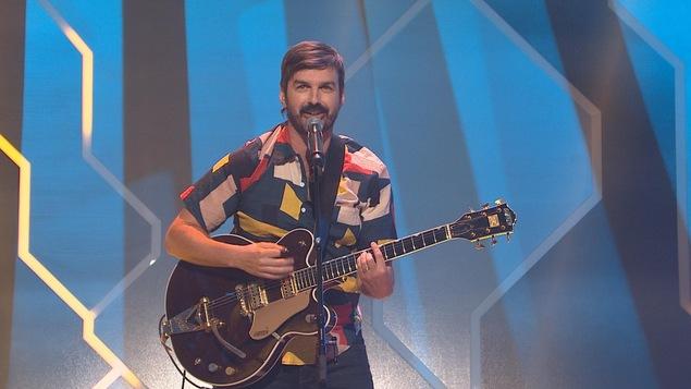 Il chante et tient une guitare en bandoulière.
