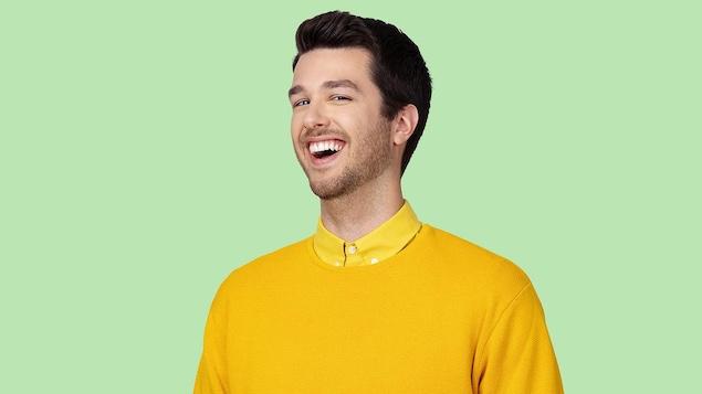 Il est habillé tout en jaune et fait un grand sourire.
