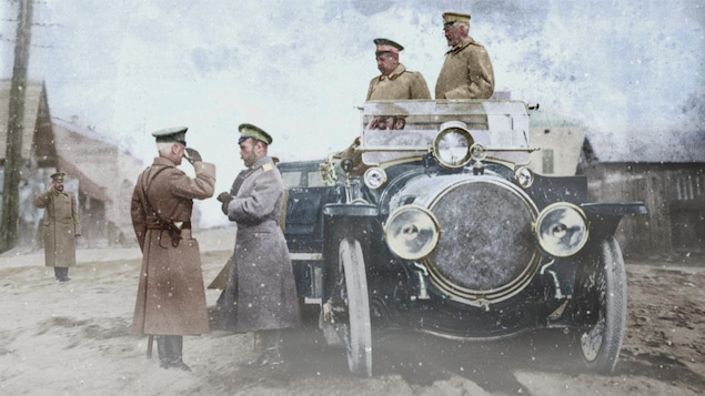 Trois soldats sont dans une voiture alors que l'un d'entre eux est débarqué pour saluer un autre soldat dans la rue.