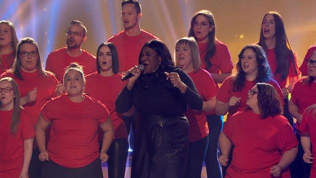 La chanteuse et comédienne se tient au milieu d'une chorale.