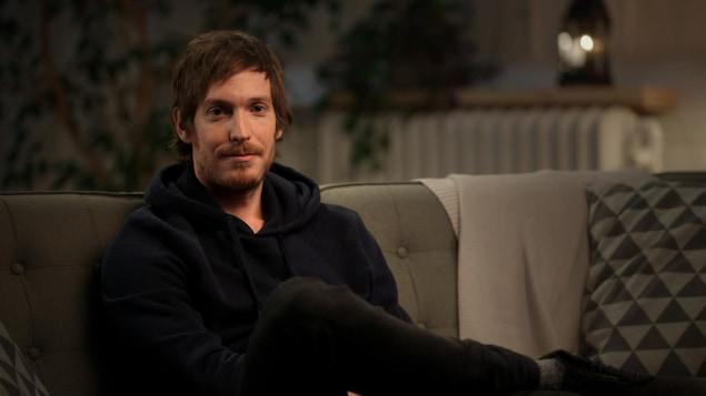 Il est assis dans un canapé.