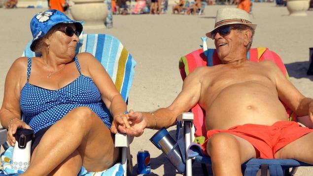 Gigi et Jean se tiennent par la main et se sourient.
