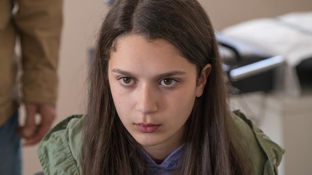 Gros plan sur le visage de la jeune fille. Elle est sérieuse. Elle a les cheveux et les yeux bruns. Ses cheveux sont longs et détachés.