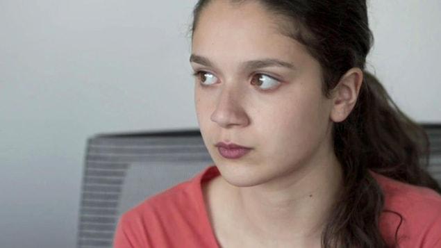 Une jeune fille aux yeux et aux cheveux bruns. Elle fixe attentivement quelqu'un ou quelque chose.