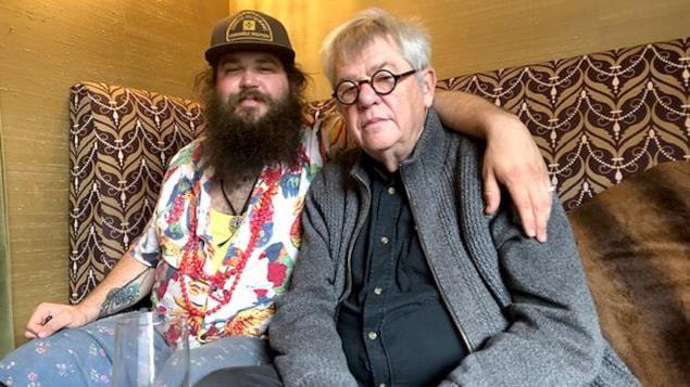 Un jeune homme portant barbe, casquette et chemise fleurie, le bras autour des épaules d'un homme portant lunettes et gilet gris, tous les deux assis sur un canapé.