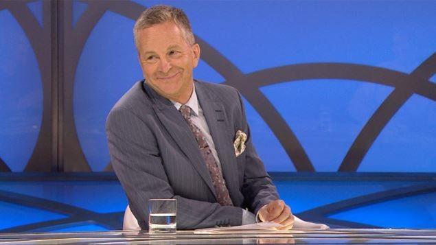 Il est souriant en veston cravate et a un verre d'eau devant lui.