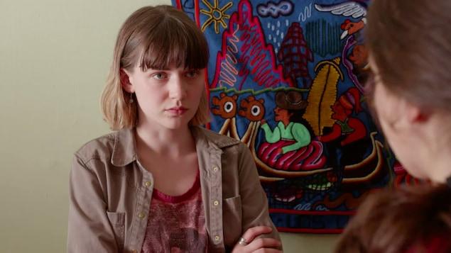 La jeune femme a les bras croisés. Elle a un air sérieux.
