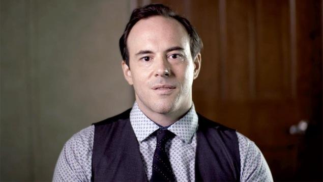Fred Eric Salvail porte une chemise à motifs, une cravate et une veste sans manches.