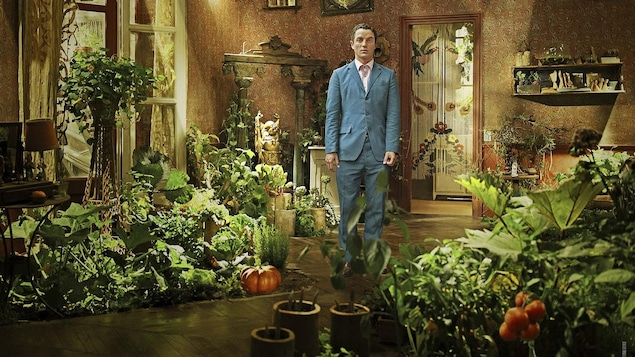 Un homme en costume bleu debout dans une pièce remplie de plantes et de légumes.