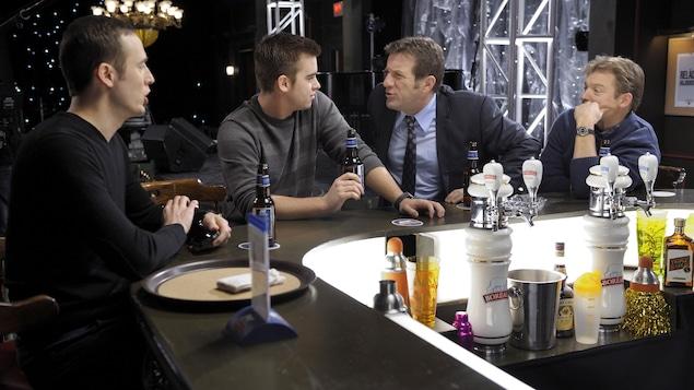Les quatre personnages sont assis au bar et discutent.