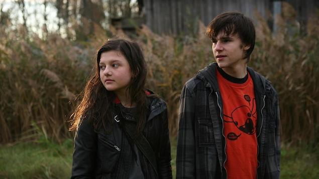 Une jeune fille et un jeune garçon dans un champ, regardent vers la gauche.