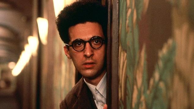 Un homme portant des lunettes penché dans le cadre d'une porte, dans un couloir.
