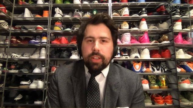 Il est dans son placard rempli de chaussures et est en veston-cravate.