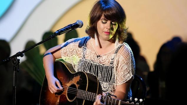 Sur le plateau de Bonsoir bonsoir, Lisa LeBlanc est assise sur un tabouret et joue de la guitare.