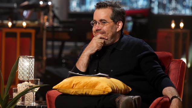 L'homme est assis en studio avec un coussin sur les genoux et il se tient le menton avec sa main.