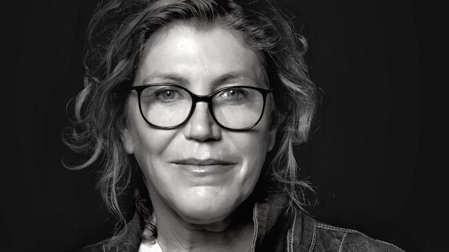 Une femme qui porte des lunettes et une veste de jeans.