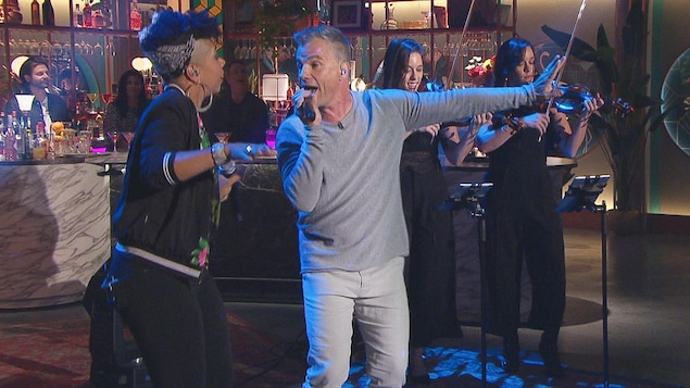 Il chante. Il porte un chandail et un pantalon gris.